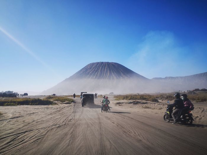People riding motorcycles on desert against blue sky