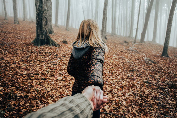 Cropped hand of man holding woman at forest during autumn
