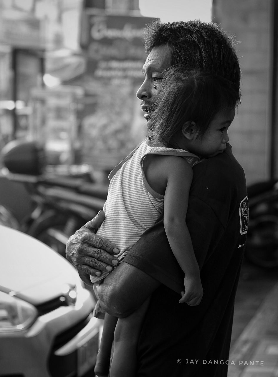 real people, childhood, two people, love, togetherness, car, focus on foreground, happiness, boys, lifestyles, side view, outdoors, standing, day, bonding, building exterior, people