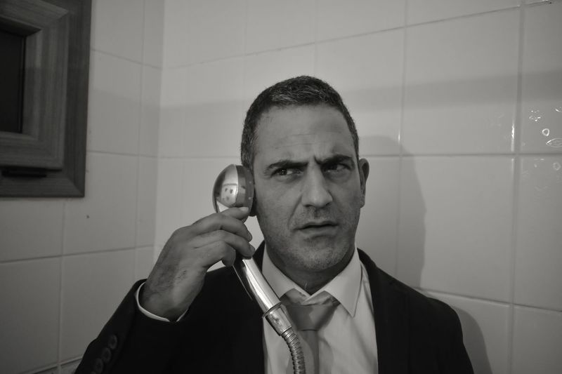 Man in suit staying in bathroom and listening shower head like talking on the phone. Simulated telephone conversation with a shower head Serviceman Communication Problems Repair Of Communications ShowerTime Sailing Aktor Imitation Shower Head One Person Headshot Portrait Men Indoors  Business Adult Telephone Communication Front View Business Person Technology Suit Phone Cord Businessman Using Phone Landline Phone