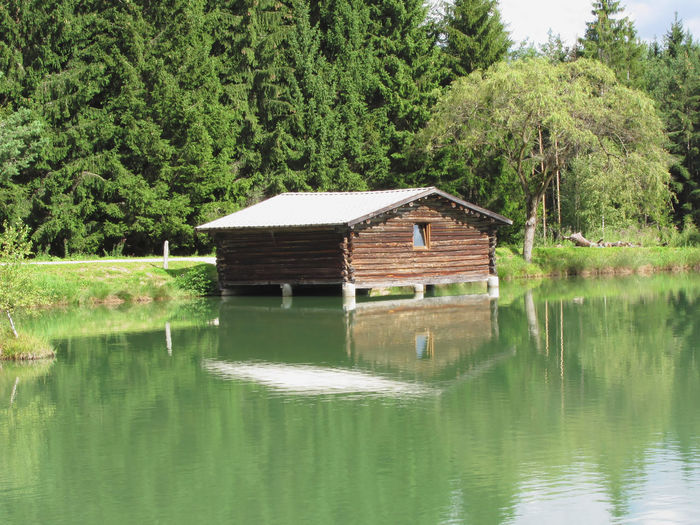 Small mountain lake with house over water and forest background . Fiè allo sciliar, South Tyrol, Italy Alpine Aqua Blue Destination Dolomites Emerald Fiè Allo Sciliar Forest Hiking Home House Italy Lake Mountain Over Water Palafitte Park Pilework Scenics Sciliar Stilts Summer Travel Tyrol Water