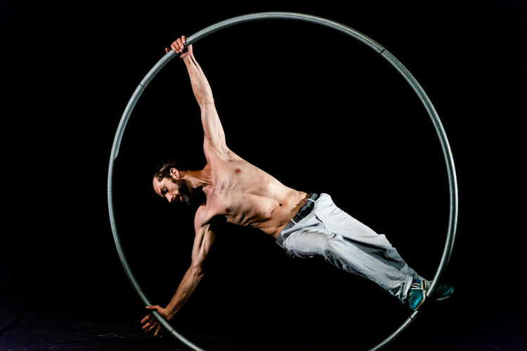 Circus Acrobat Adult Arts Culture And Entertainment Balance Black Background Circus Concentration Dancing Effort Exercising Flexibility Hairstyle Healthy Lifestyle Indoors  One Person Performance Plastic Hoop Shirtless Skill  Sport Strength Studio Shot Young Adult