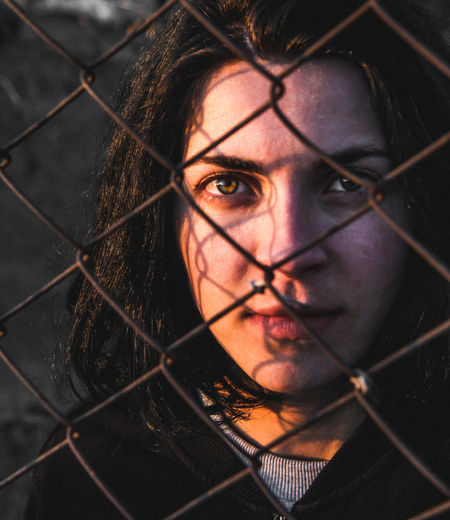 Close-up portrait of young woman against chainlink fence