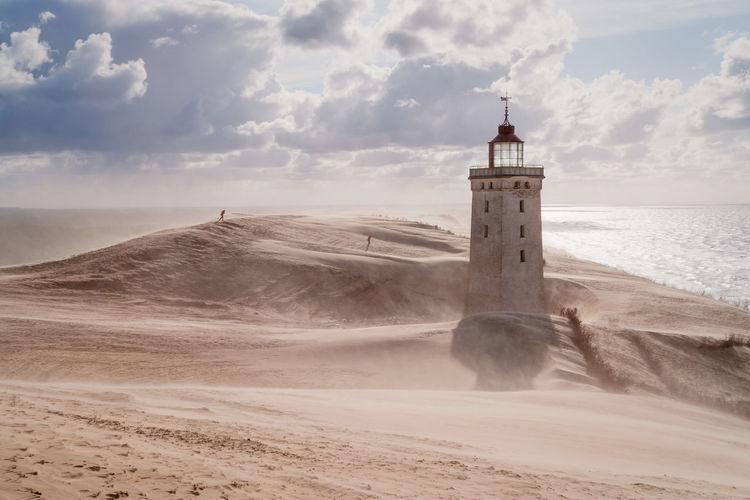 Rubjerg Knude Lighthouse On Coast Against Cloudy Sky