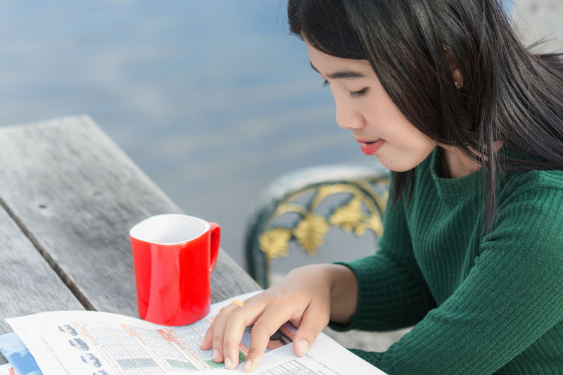 Young woman reading document by coffee on table at sidewalk cafe