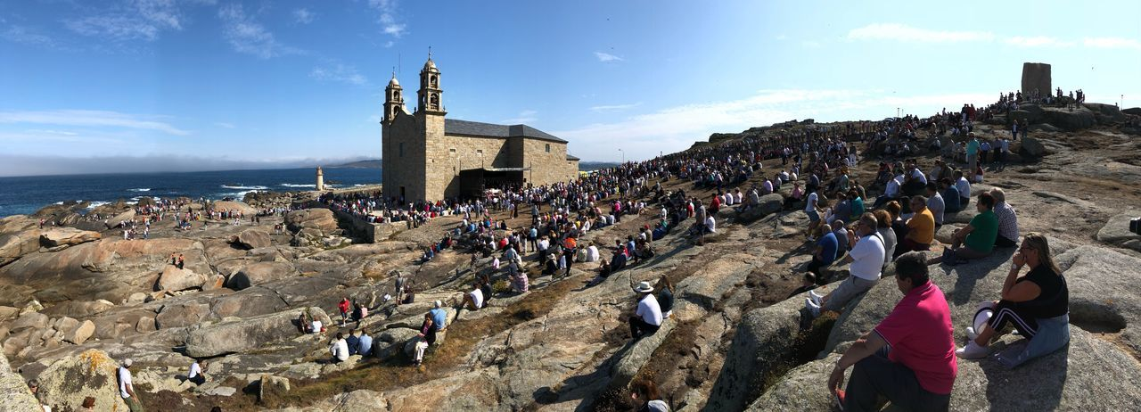 Panoramic view of people sitting on rock formation by sea against sky