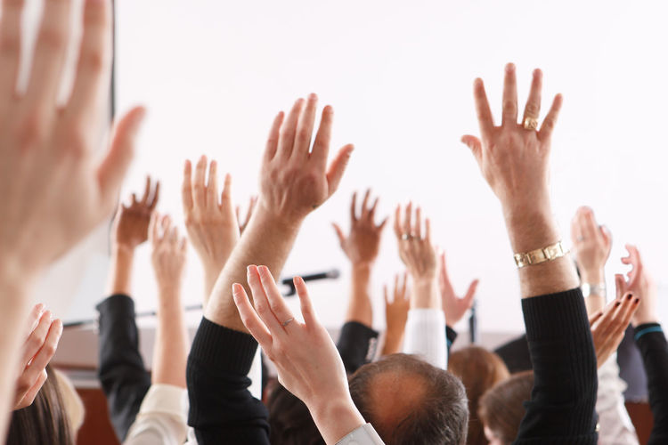 Cropped image of hands raised at seminar
