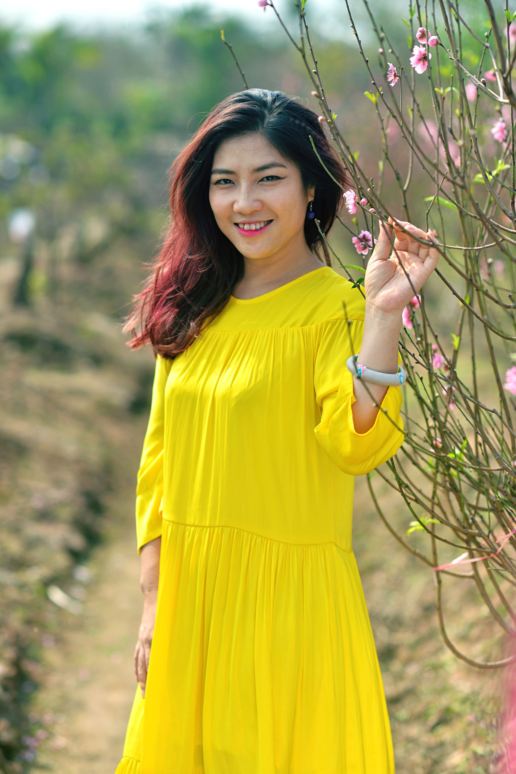 yellow, one person, smiling, portrait, beauty, looking at camera, casual clothing, outdoors, people, happiness, standing, tree, adults only, day, human arm, human body part, nature, close-up, adult, bangle