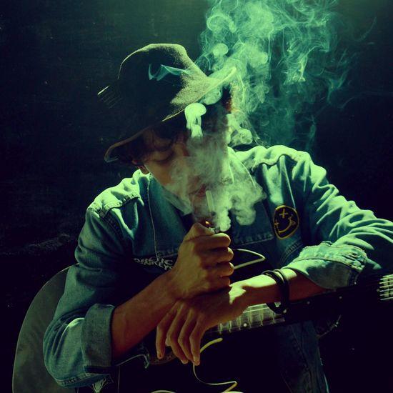 Man holding cigarette against black background