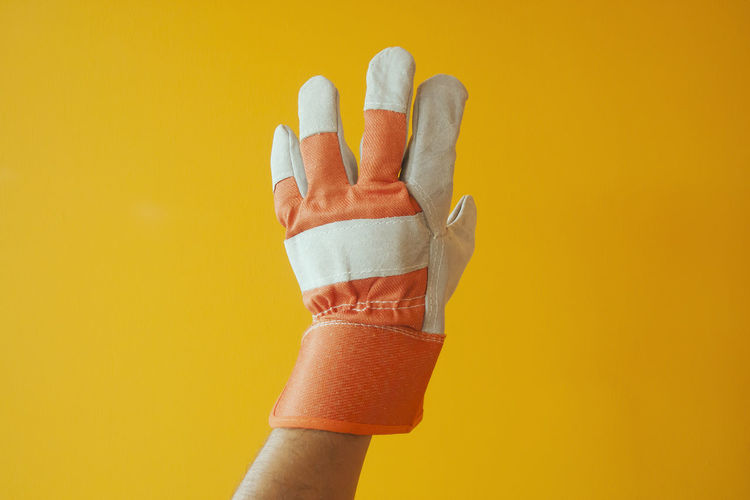 Close-up of hand wearing gloves gesturing against yellow background