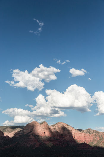 Low angle view of rocky mountain against blue sky