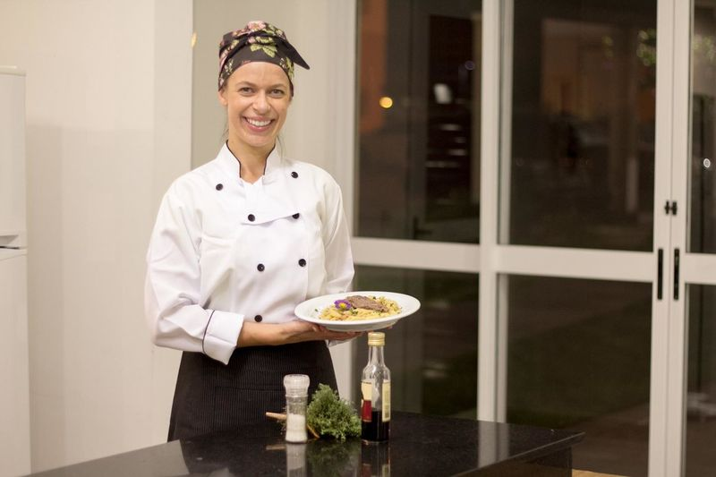 Portrait of happy female chef holding food in plate while standing in commercial kitchen