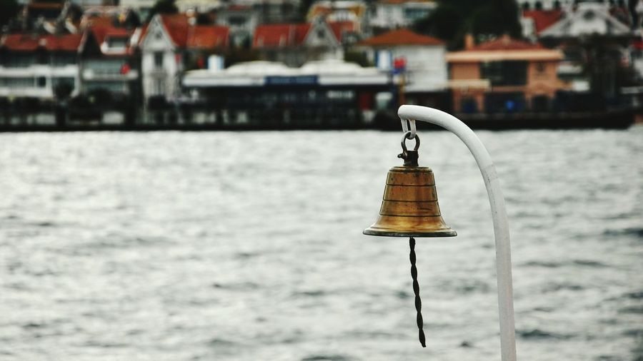 Close-up of chain hanging over sea against blurred background