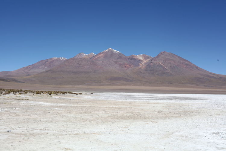 Scenic view of salt desert with mountains in background against blue sky