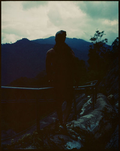 Rear view of silhouette man standing against mountain