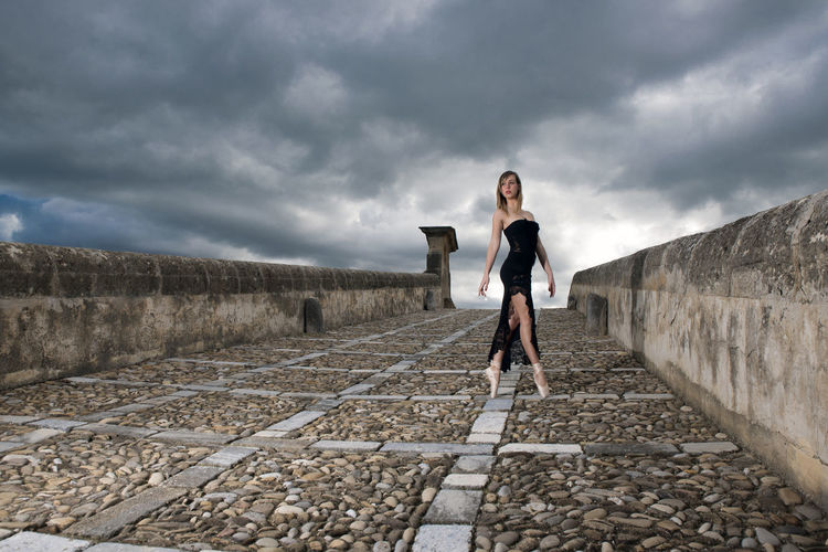 Full length of young woman on walkway against cloudy sky