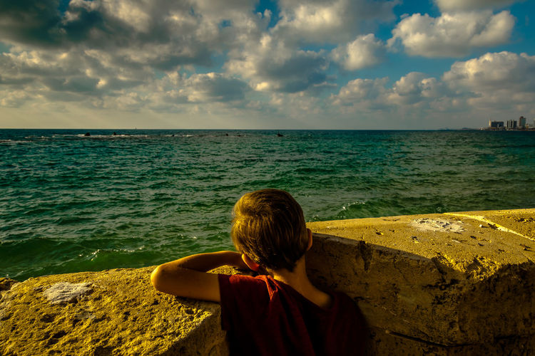 Rear view of boy standing by retaining wall in front of sea