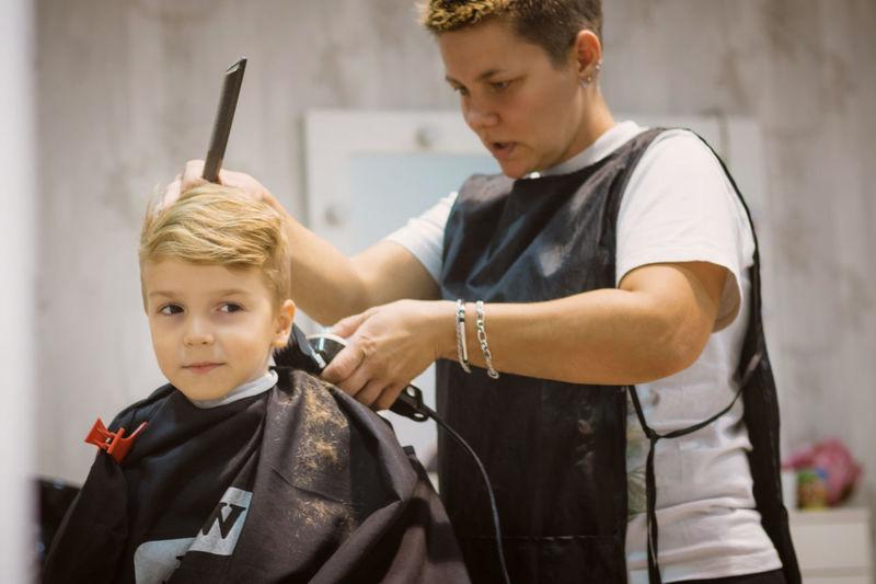Female hairdresser styling boy hair in salon
