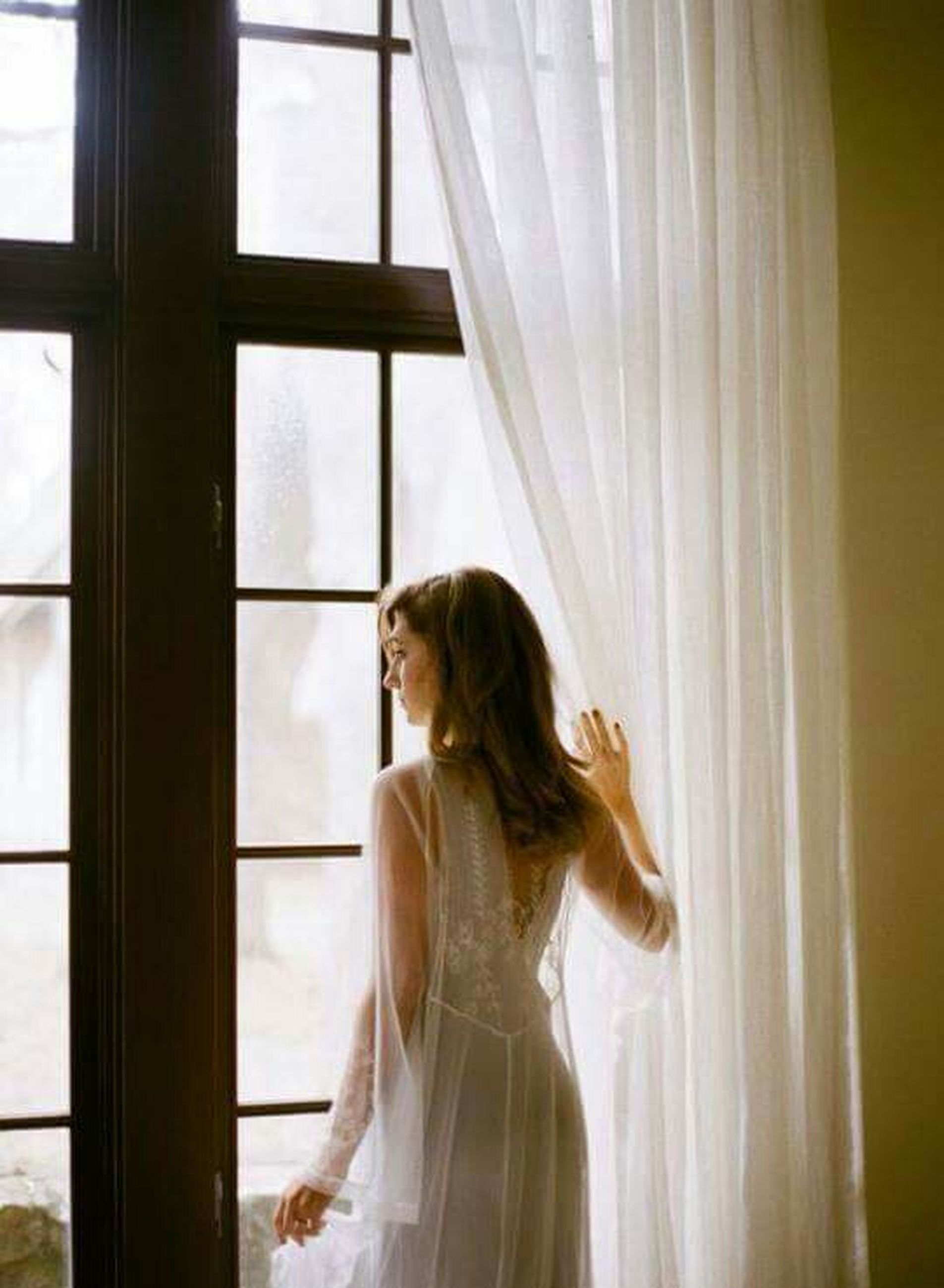 indoors, window, lifestyles, young women, young adult, curtain, long hair, standing, person, waist up, leisure activity, three quarter length, home interior, rear view, casual clothing, contemplation