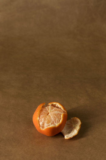 A single half-peeled clementine on brown paper - minimal Citrus  Freshness Minimalist Brown Brown Paper Citrus Fruit Clementine Clementines Foodphotography Fruit Healthy Healthy Eating Healthy Food Ingredient Mandarins Minimal Minimalism Monochromatic Monochrome Mood Obst Orange Color Peel Peeling Pile Still Life