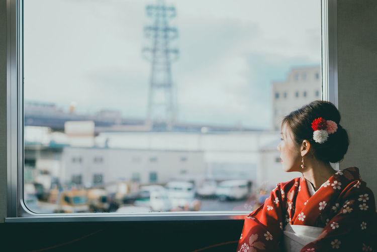 Woman wearing kimono looking through window at home