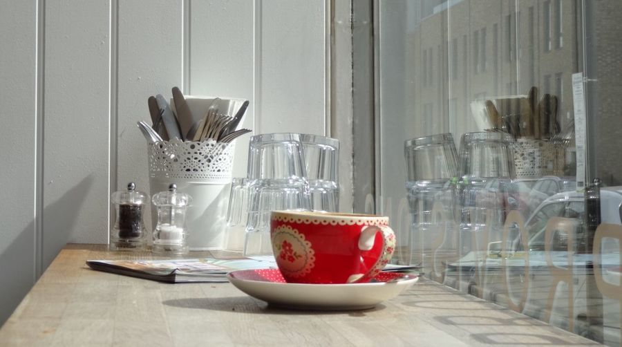 Red cup and saucer on wooden table