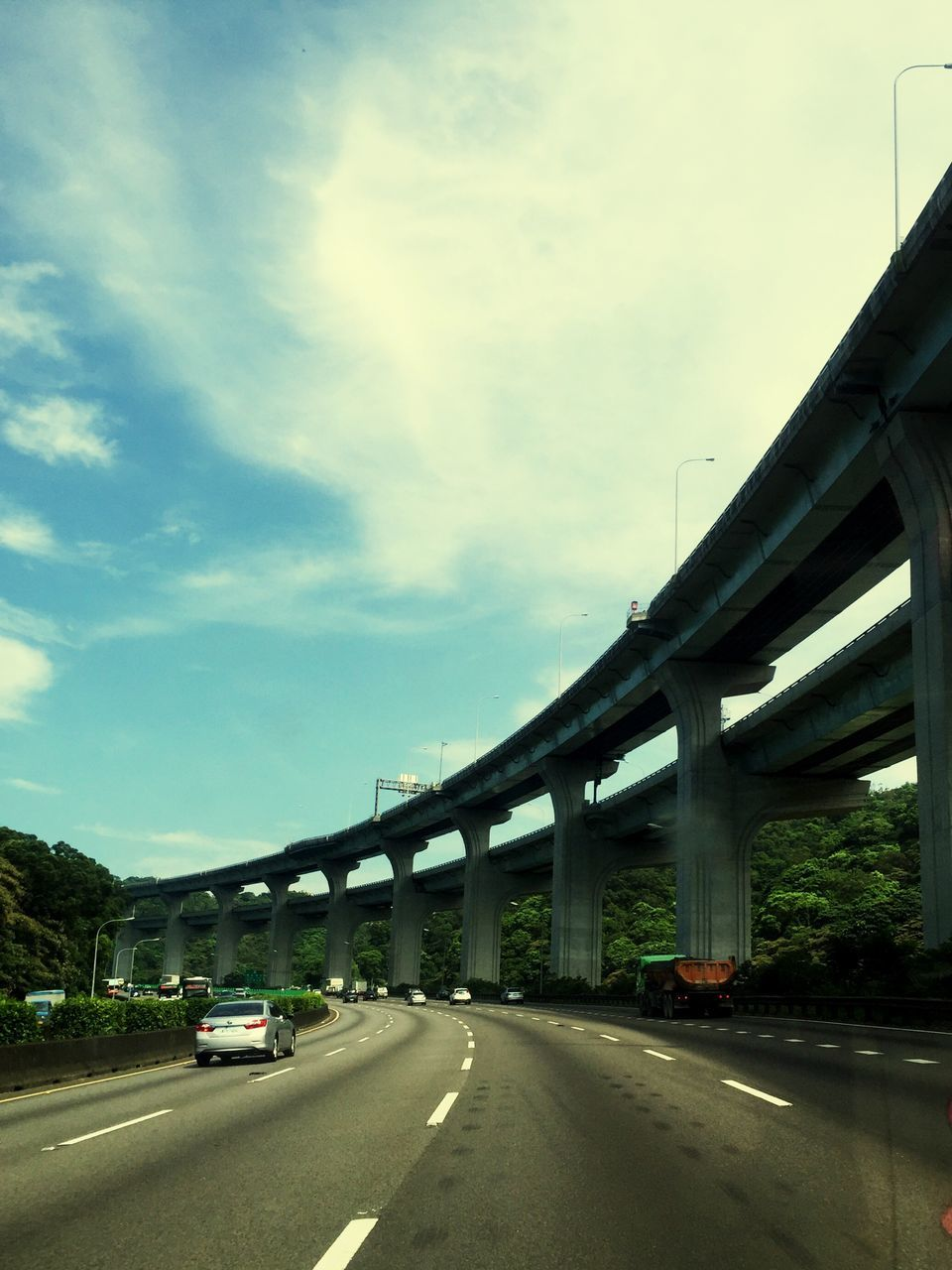 transportation, bridge - man made structure, road, connection, car, sky, mode of transport, the way forward, land vehicle, cloud - sky, architecture, outdoors, built structure, day, no people, nature, tree, city