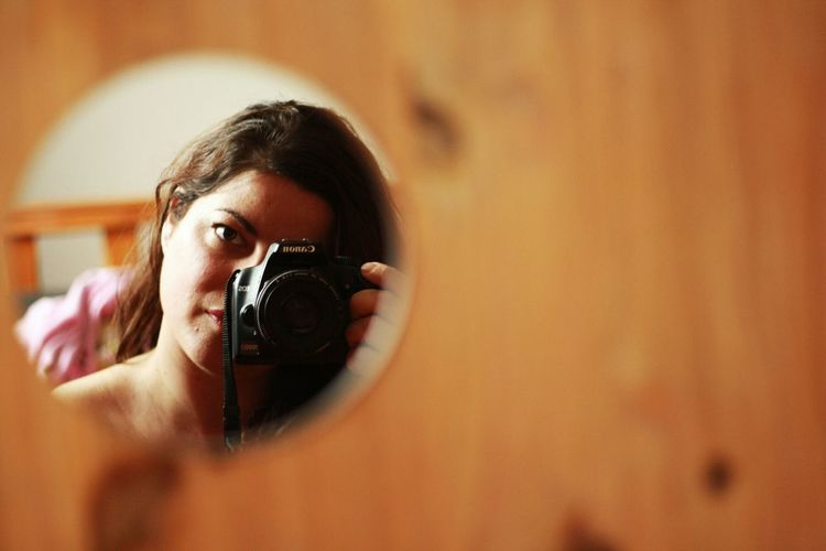 Portrait of young woman holding camera