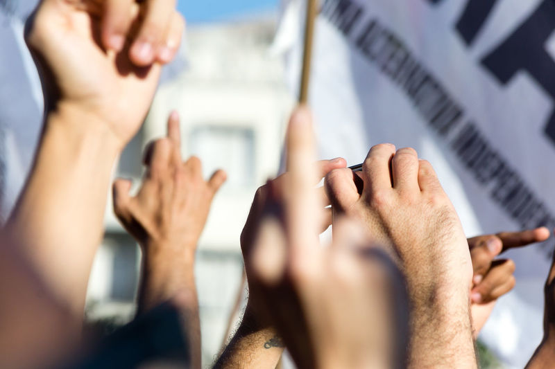 Close-Up Of Raised Hands Outdoors