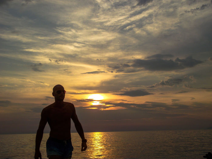 Man at beach against sky during sunset