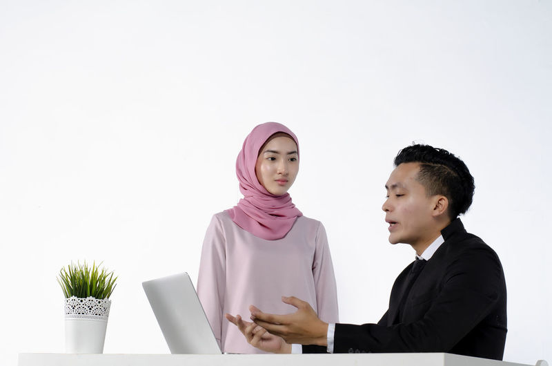 portrait of young couple entrepreneurs discussing ideas with a laptop in front of them Business Office Indoors  White Background Young Men Laptop Waist Up People Adult Young Adult Two People Front View Business Person Occupation Communication Computer Copy Space Looking Real People Wireless Technology Using Laptop