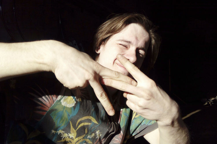 Young man gesturing peace sign at home
