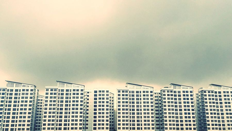 Low angle view of buildings against cloudy sky