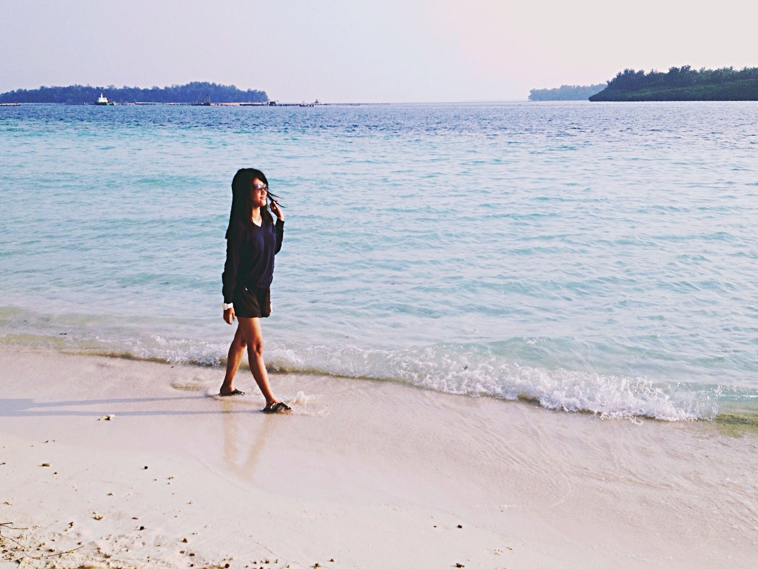 sea, beach, water, horizon over water, shore, full length, sand, lifestyles, leisure activity, vacations, standing, casual clothing, wave, tranquility, tranquil scene, beauty in nature, rear view, scenics