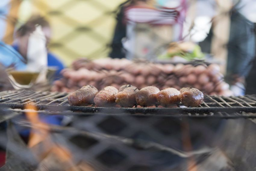 Close up of a group of sausages roasting on a grill. Food Food And Drink Barbecue Selective Focus Freshness Meat Barbecue Grill Incidental People Grilled Day Heat - Temperature Close-up Preparation  Preparing Food Outdoors Wellbeing Market Healthy Eating Sausage Retail  Street Food