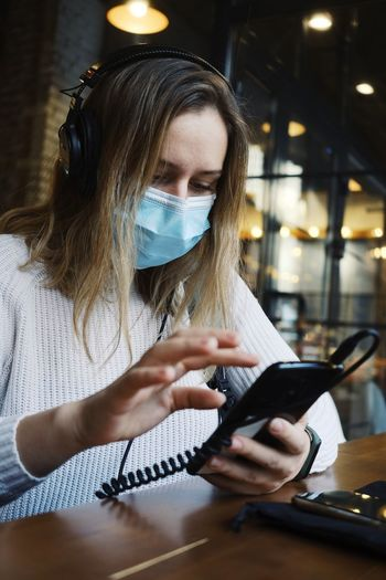 Woman wearing mask using smart phone sitting at cafe