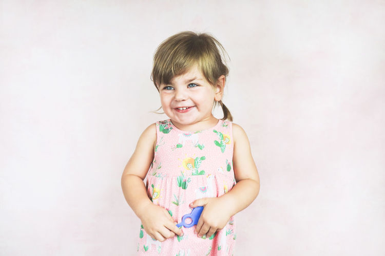 Looking At Camera Portrait Childhood Child Studio Shot One Person Smiling Indoors  Emotion Happiness Girls Innocence Front View White Background Women Standing Casual Clothing Offspring Bangs Floral Pattern Hairstyle Excitement Cute Adorable Lovely