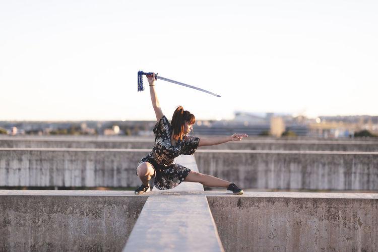 Full length of man skateboarding on city against clear sky