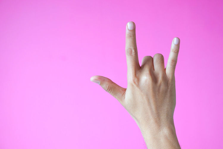 Close-up of human hand against pink background