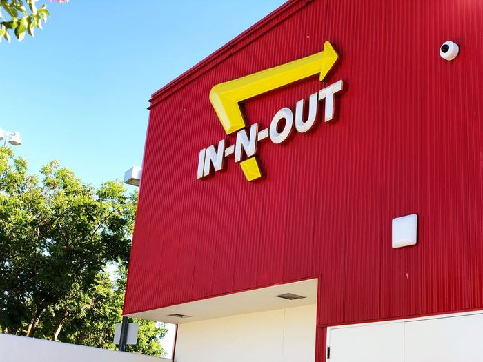 In-N-Out logo on famous red burger joint. Fast Food Popular Drive Thru In N Out Burger In-N-Out Burger Joint Building Exterior Architecture Built Structure No People Communication Sky Red Low Angle View Day Text Tree Western Script Building Capital Letter Wall - Building Feature Sign Wall Outdoors