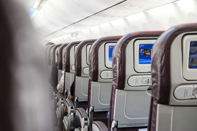 Rear view of economy class cabin seats of an airplane. Airplane Seat Boeing 737-800 Copy Space Rear View Aircraft Airplane Cabin Flying In A Row Inflight Interior Journey Seat Transportation Travel