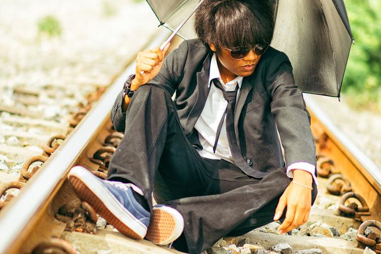 Businessman with umbrella sitting on railroad track