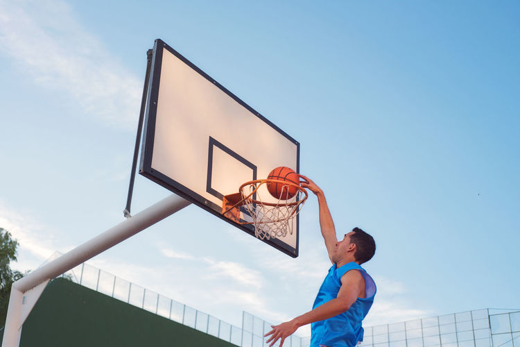 Full length of man jumping with ball by basketball hoop against sky