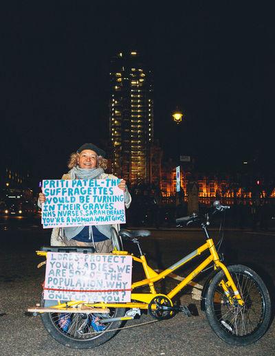 Man cycling on illuminated street against sky at night