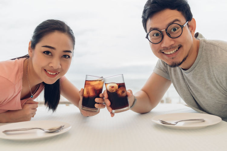 Portrait of smiling young man and woman on table