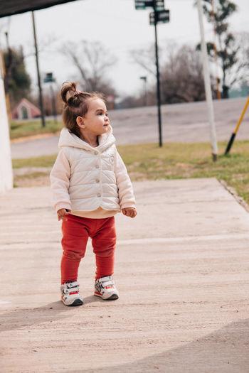 Full length of cute girl standing looking away