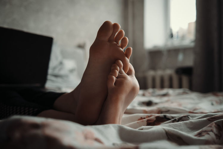 Midsection foot of woman lying on bed
