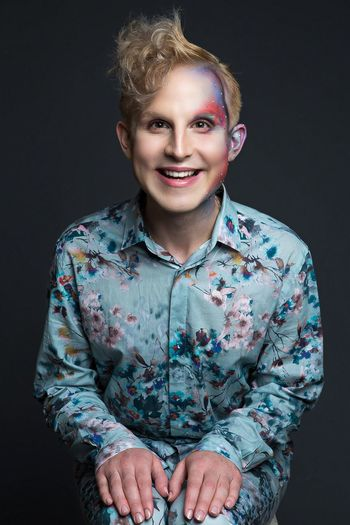 Portrait of smiling young man with make-up in floral clothing against black background