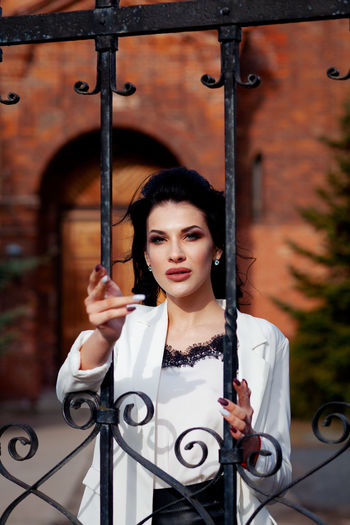 Portrait Of Beautiful Woman Standing At Gate Against Historic Building