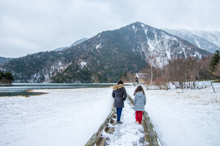 People walking on snowy pier over lake against mountains